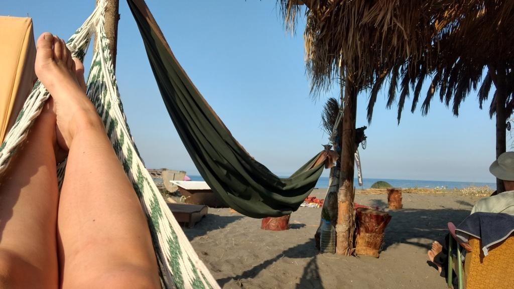 Girl hangs in hammock on a beach in Montenegro.