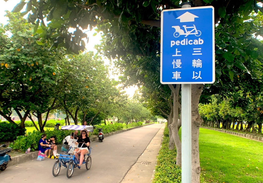 Girl sits in rickshaw in park in background, while pedicab sign is visible in foreground.