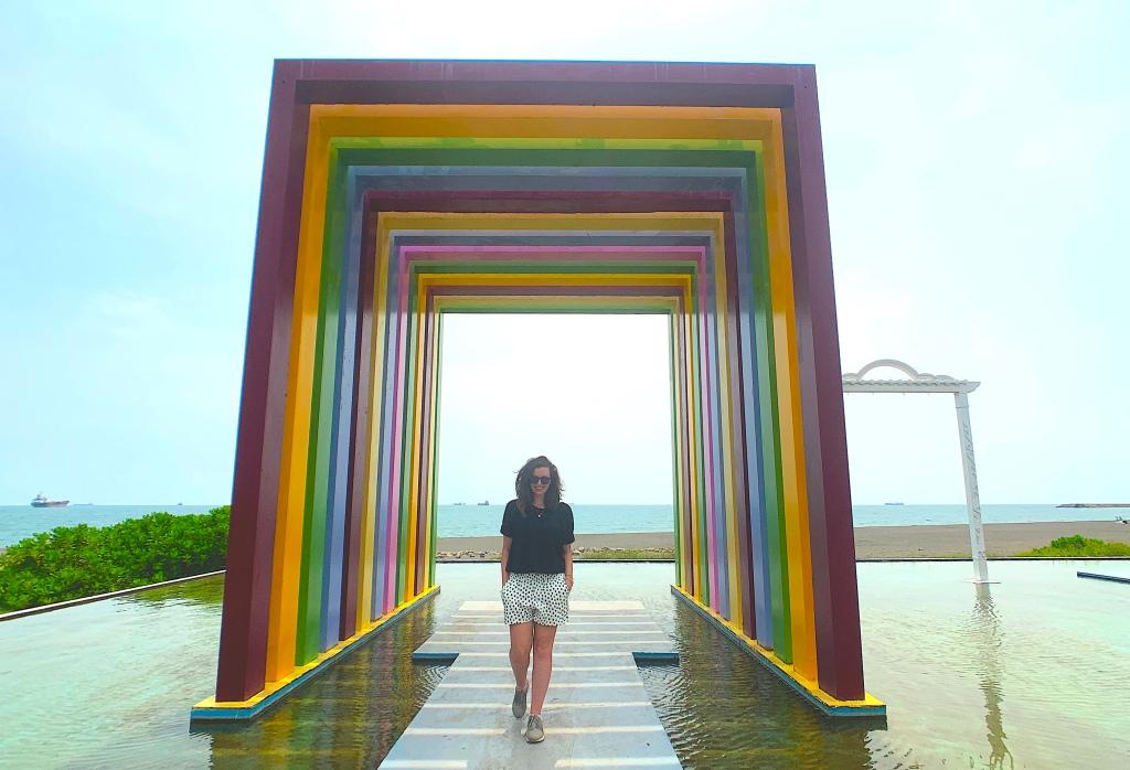 Girl walks through rainbow sculpture on Cijin Island, Kaohsiung, Taiwan.
