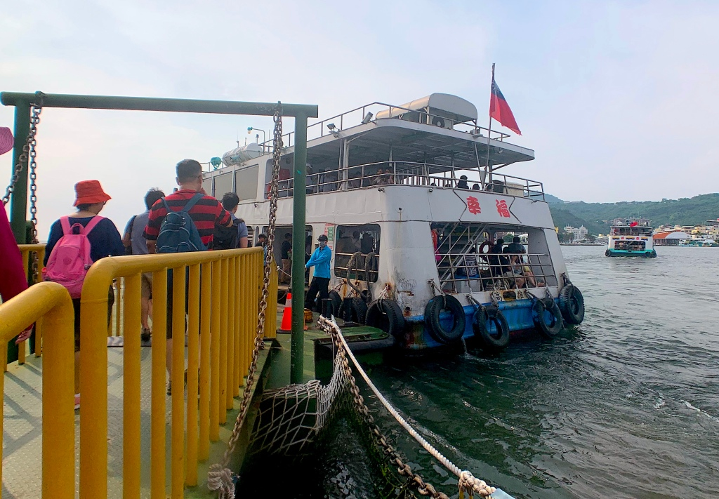 A ferry docks at Cijin Island, Kaohsiung, Taiwan while tourists prepare to get on board.