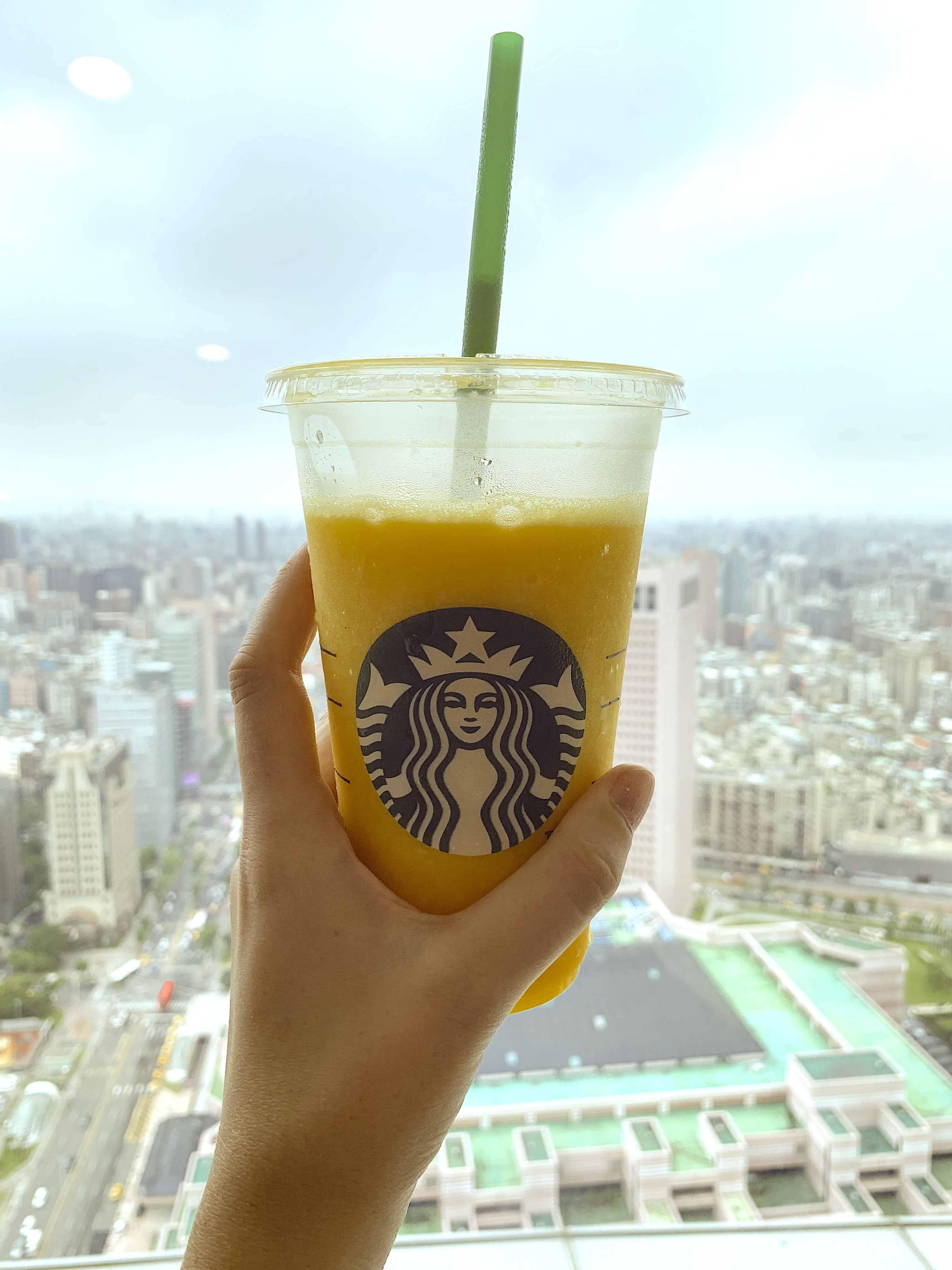 Hand-holds-Starbucks-cup-in-front-of-city-view