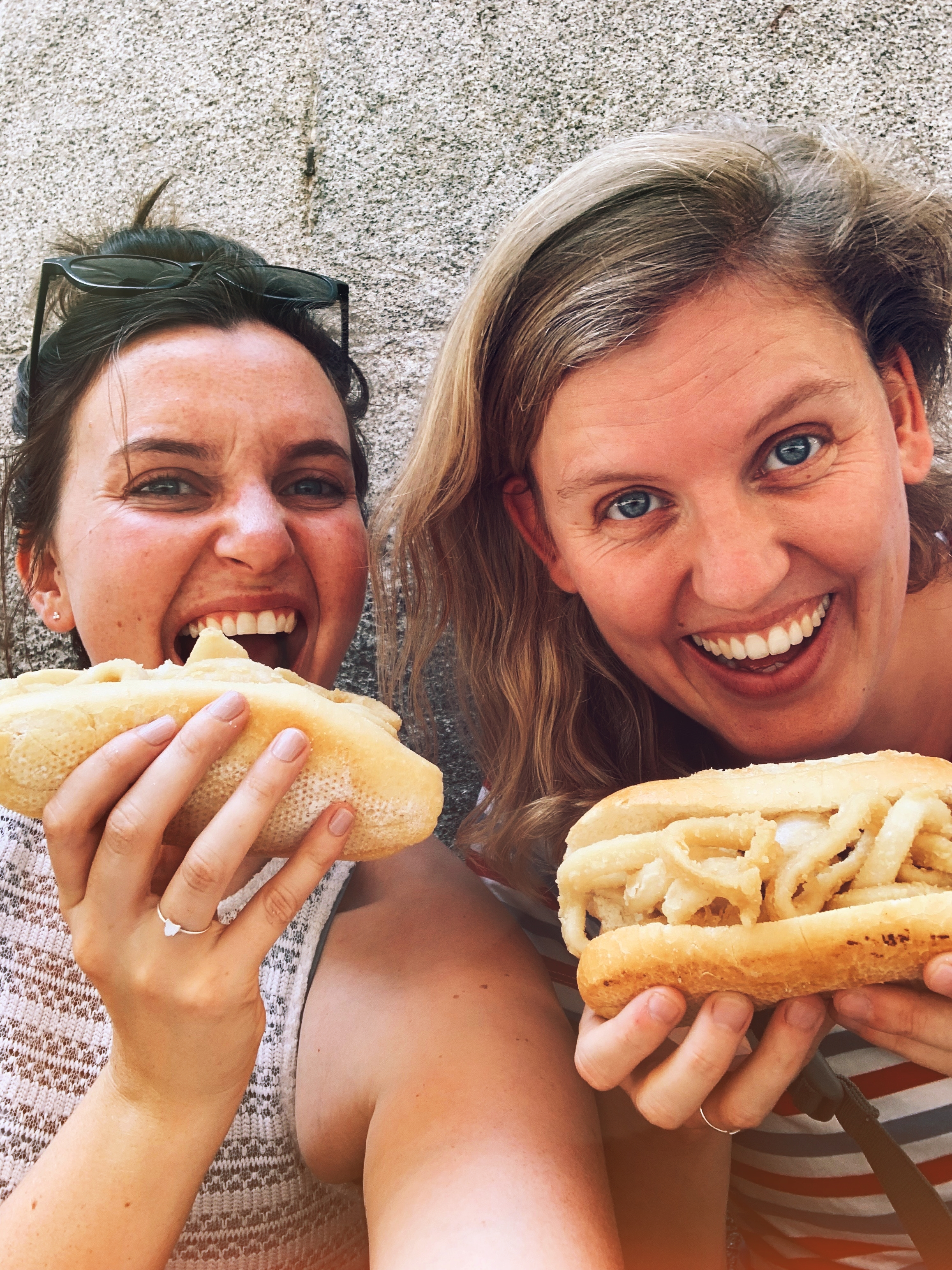 Two girls eat bocadillo de calamares in Madrid, Spain