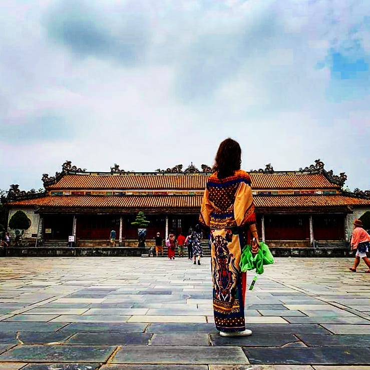 A woman in traditional clothing stands in front of Hue's Imperial Castle