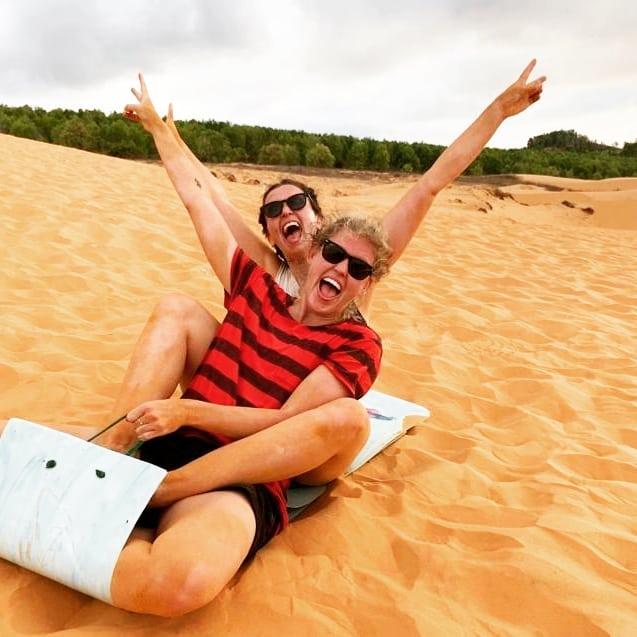 Two girls sand-boarding in Mue Ne, Vietnam