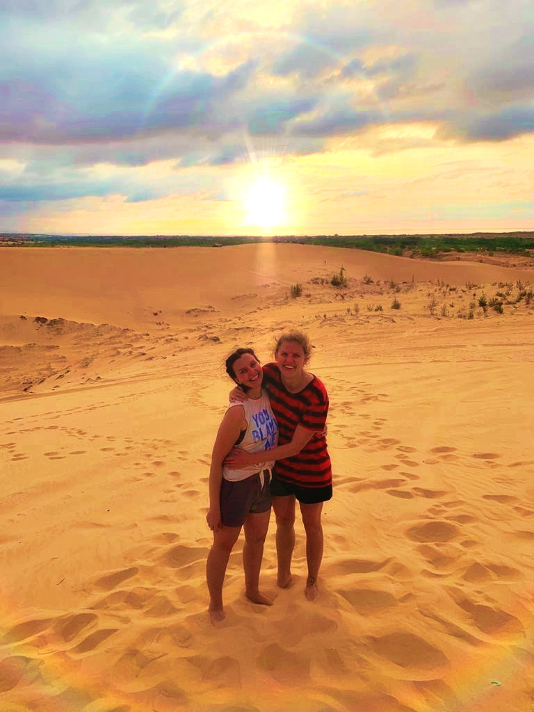 Two girls at White Sand in Mui Ne as the sun rises behind them