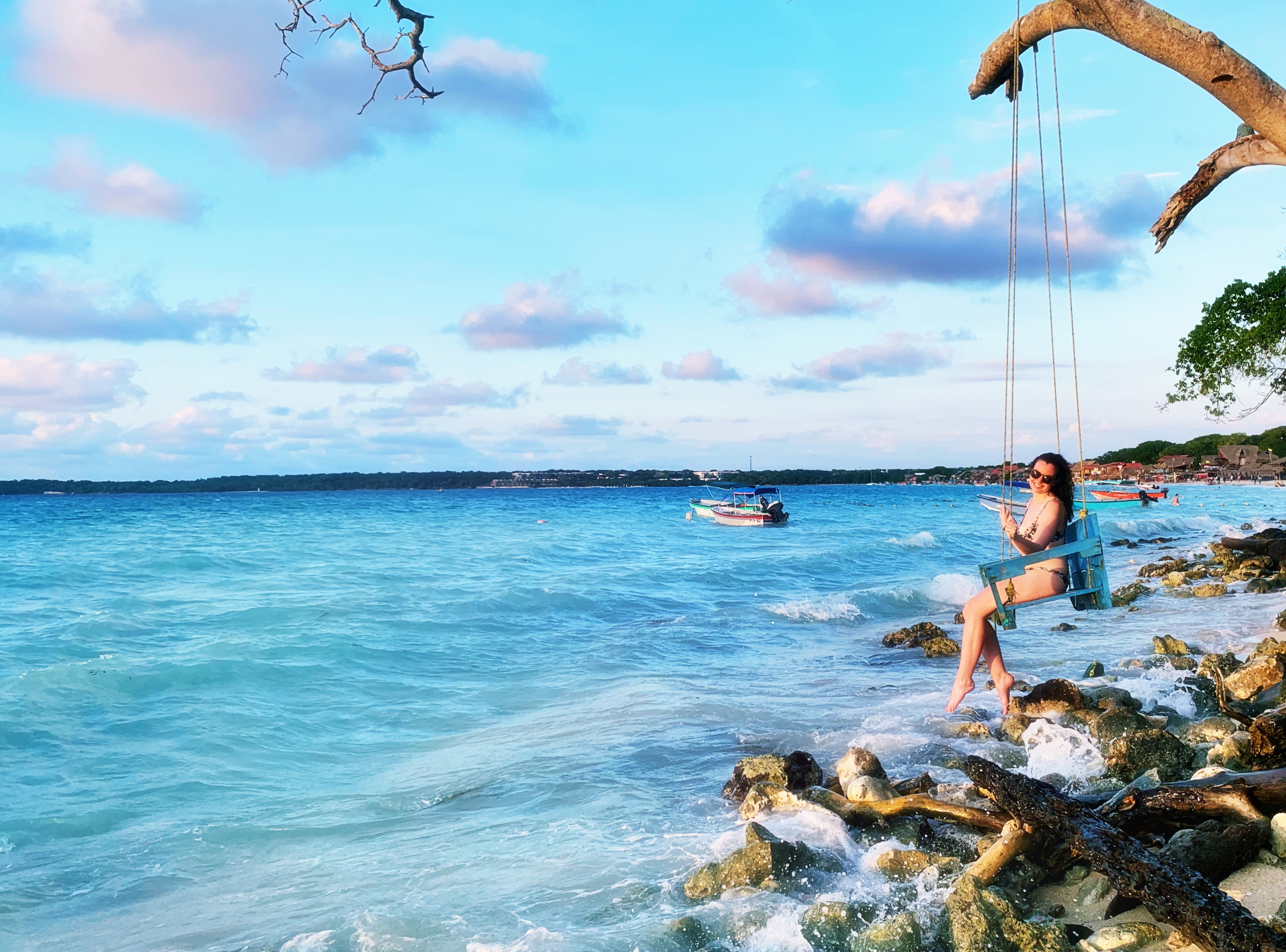 A girl swings on over the water in Playa Blanca, Colombia