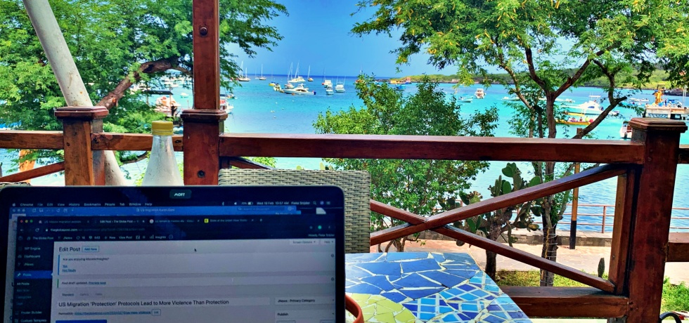 photo-of-laptop-on-table-with-galapagos-island-in-background